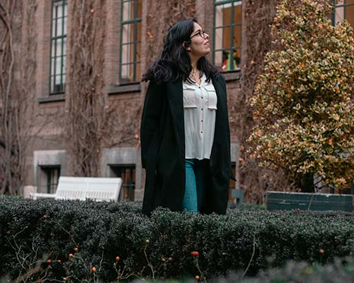 Picture of Alex, a dark hair Latina wearing a black jacket, white shirt and jeans walking through the gardens of Rotterdam City Hall.