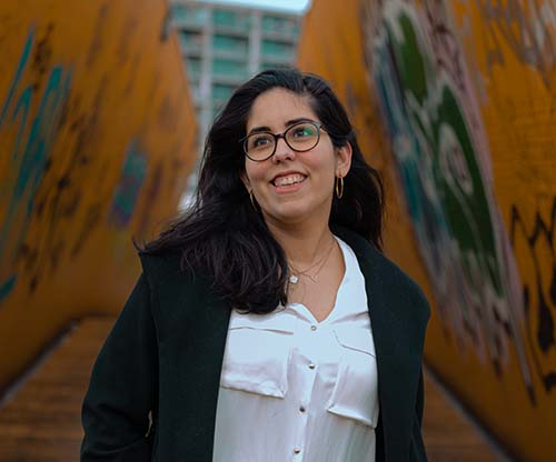 Picture of Alex, a dark hair Latina wearing a black jacket, white shirt and jeans walking and smiling at the yellow bridge in Rotterdam.